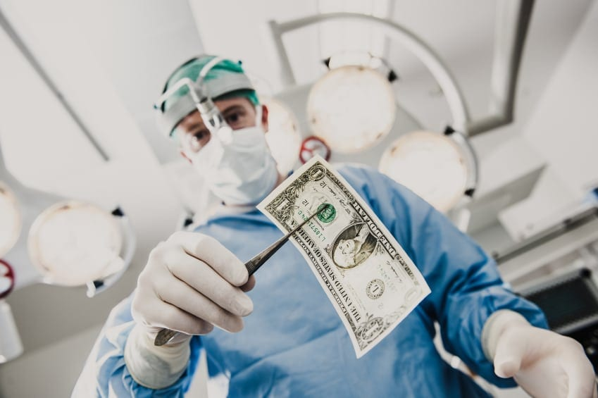 Doctor holding money with surgical instrument stock photo