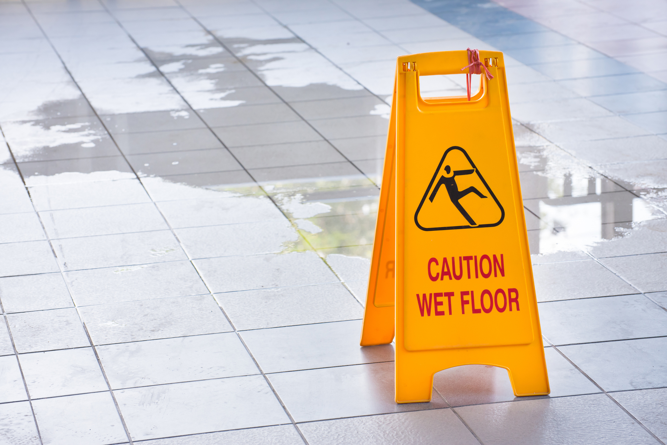 A wet floor sign by a puddle on a walkway.