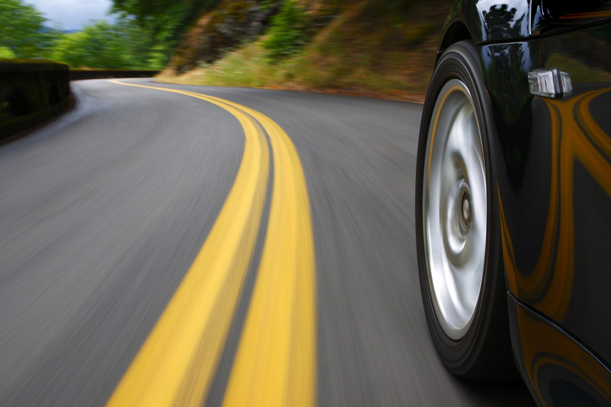 Closeup Of A Car's Tires While Driving Stock Photo