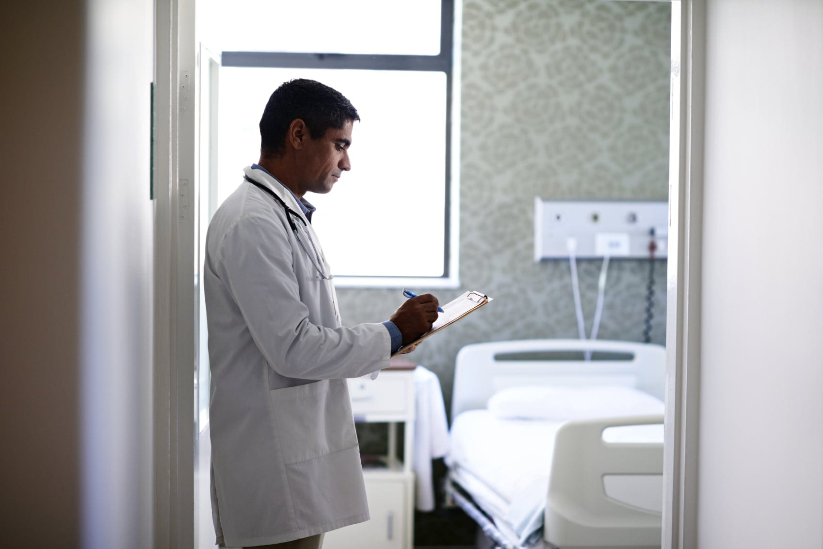 Male Doctor Filling Out Medical Form Inside Hospital Room Stock Photo