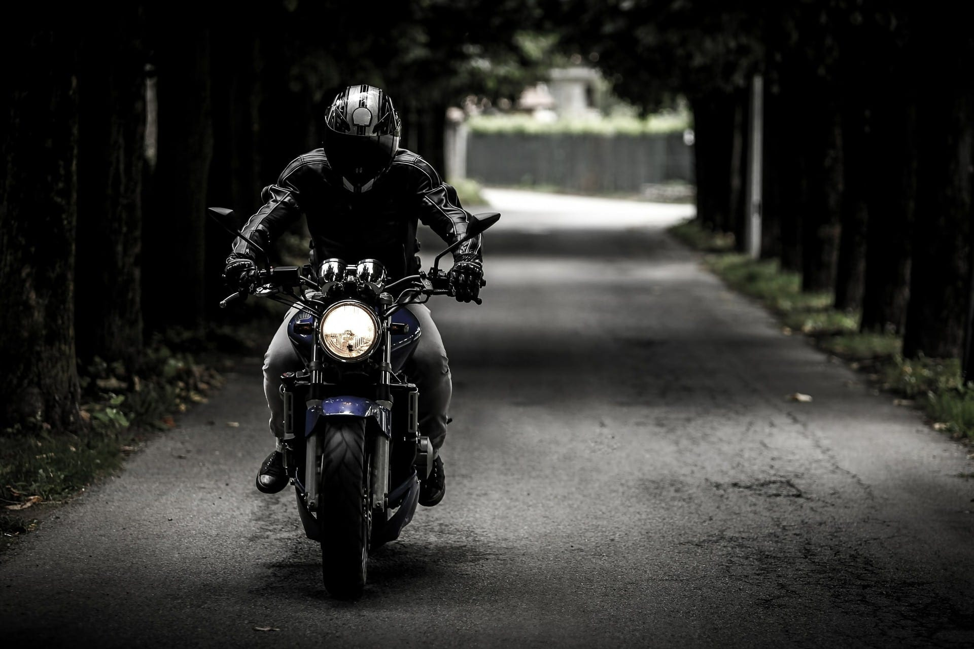 Motorcyclist Riding His Motorcycle Through An Alley Stock Photo