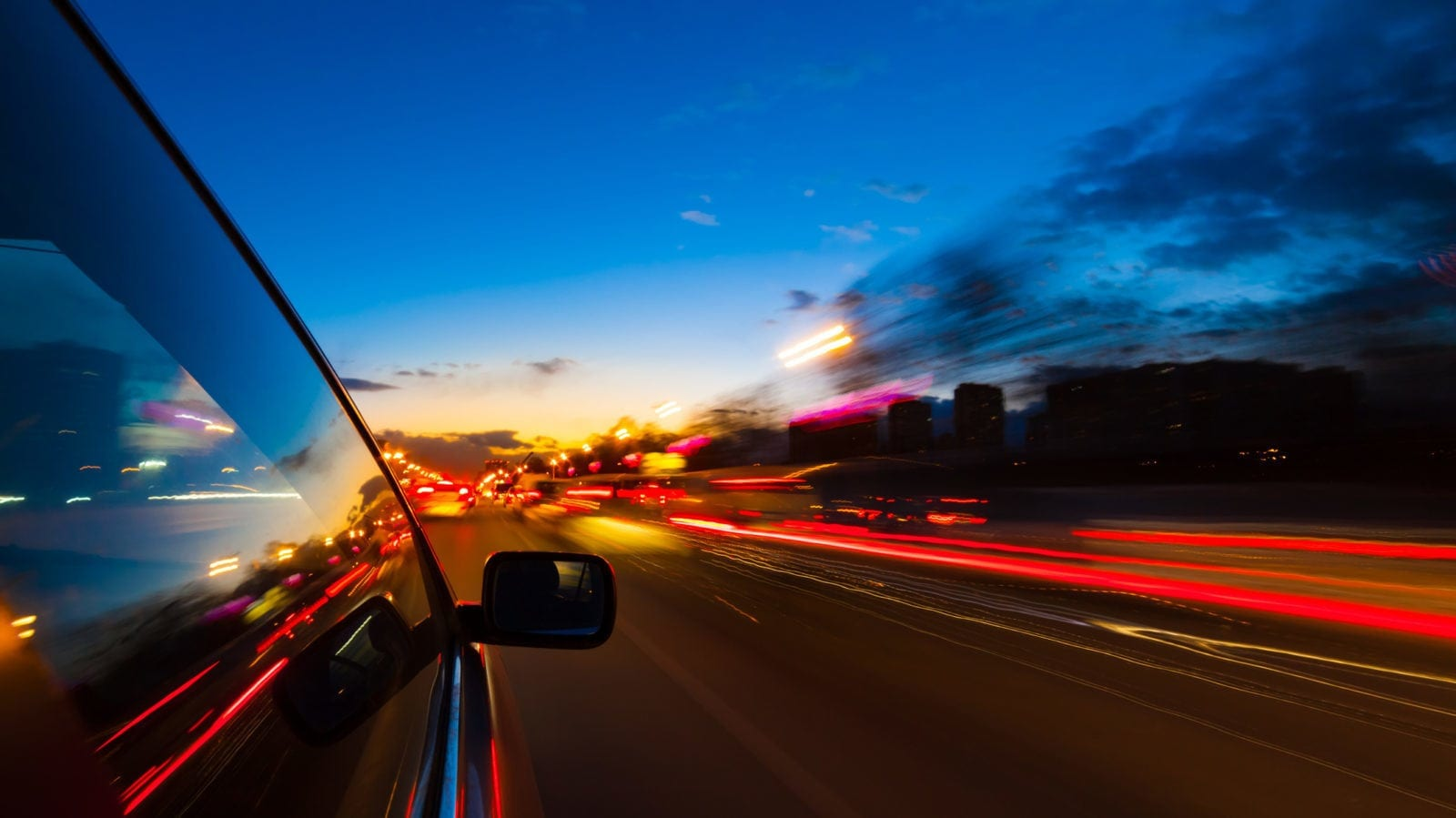 Car Driving Through A Large City At Night Stock Photo