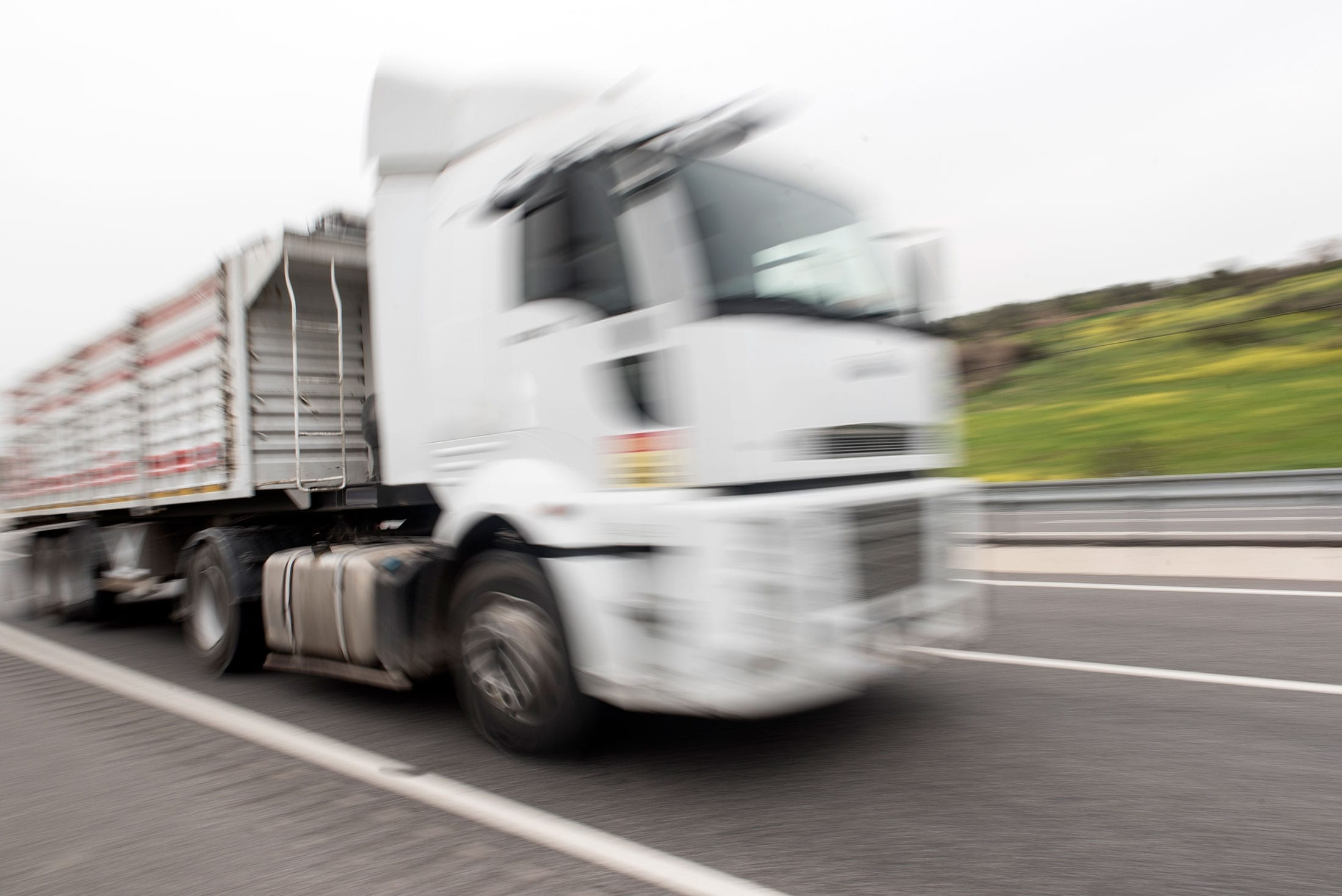 White Semi-Truck Driving On A Highway Stock Photo