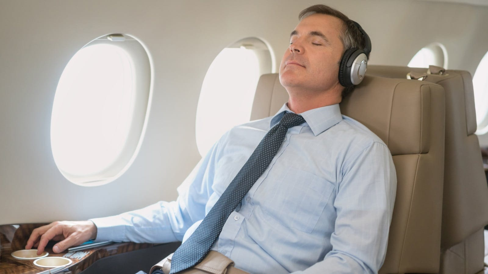 Male Passenger Resting On An Airplane Stock Photo