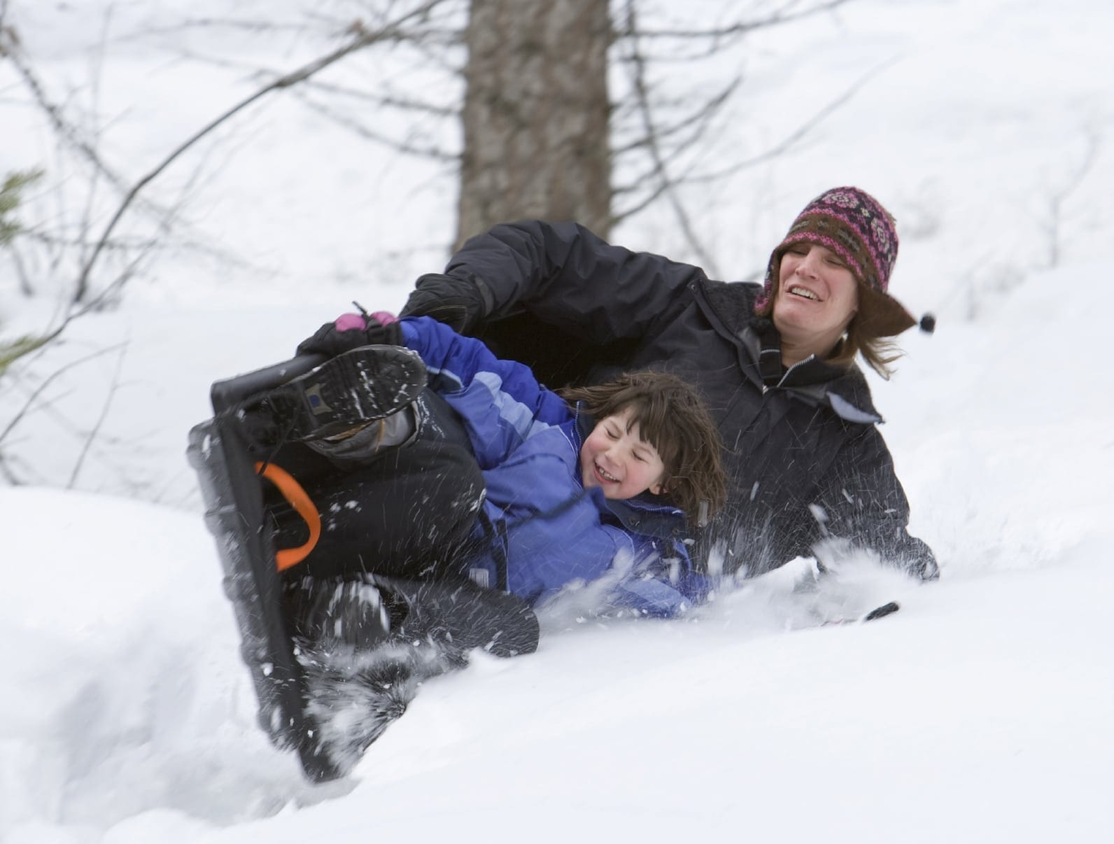 Mother and Daughter Sledding Down A Hill Stock Photo
