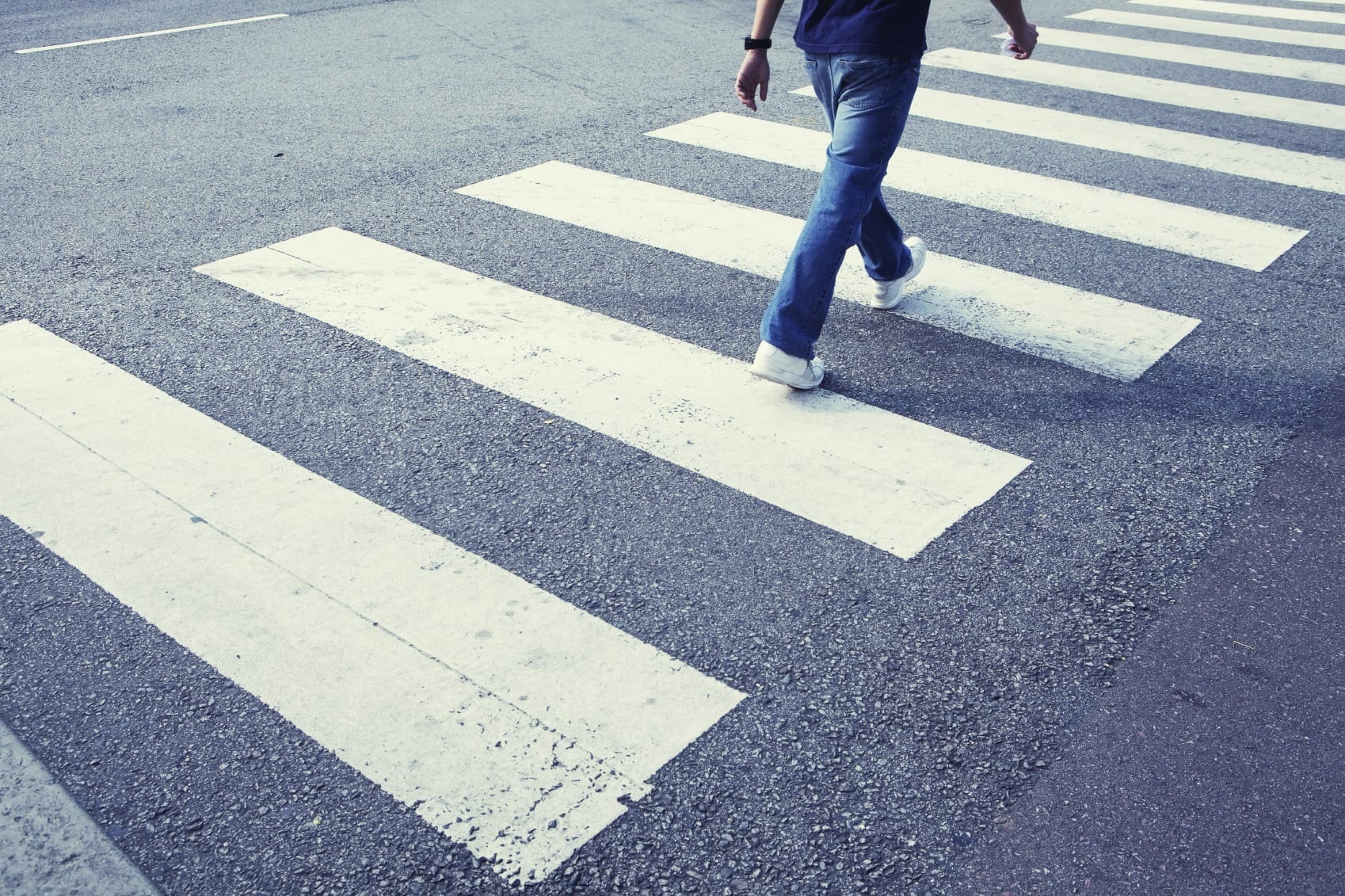 Man Walking Across The Street At A Crosswalk Stock Photo