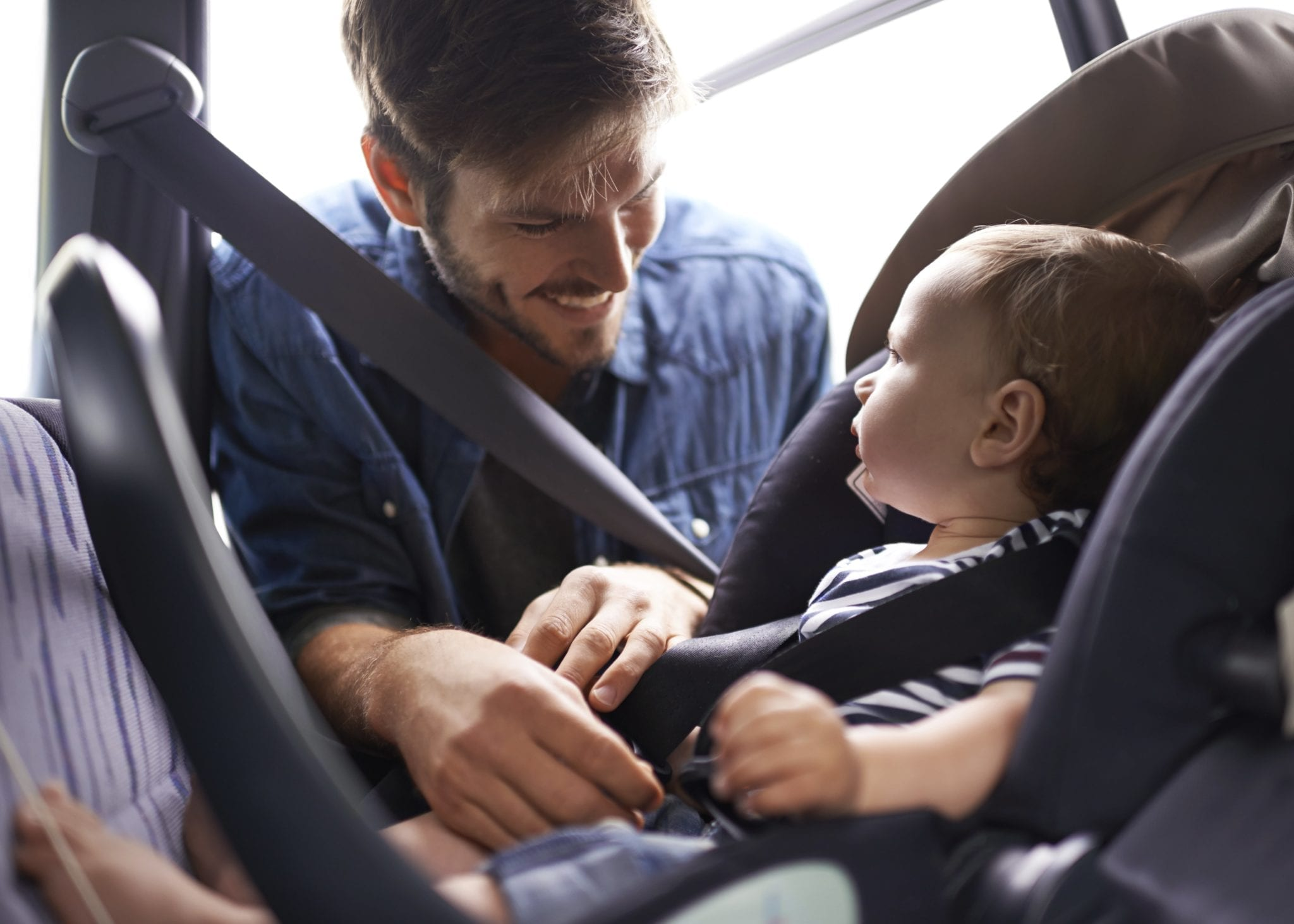 Small Child Being Fastened Into Car Seat By Father Stock Photo