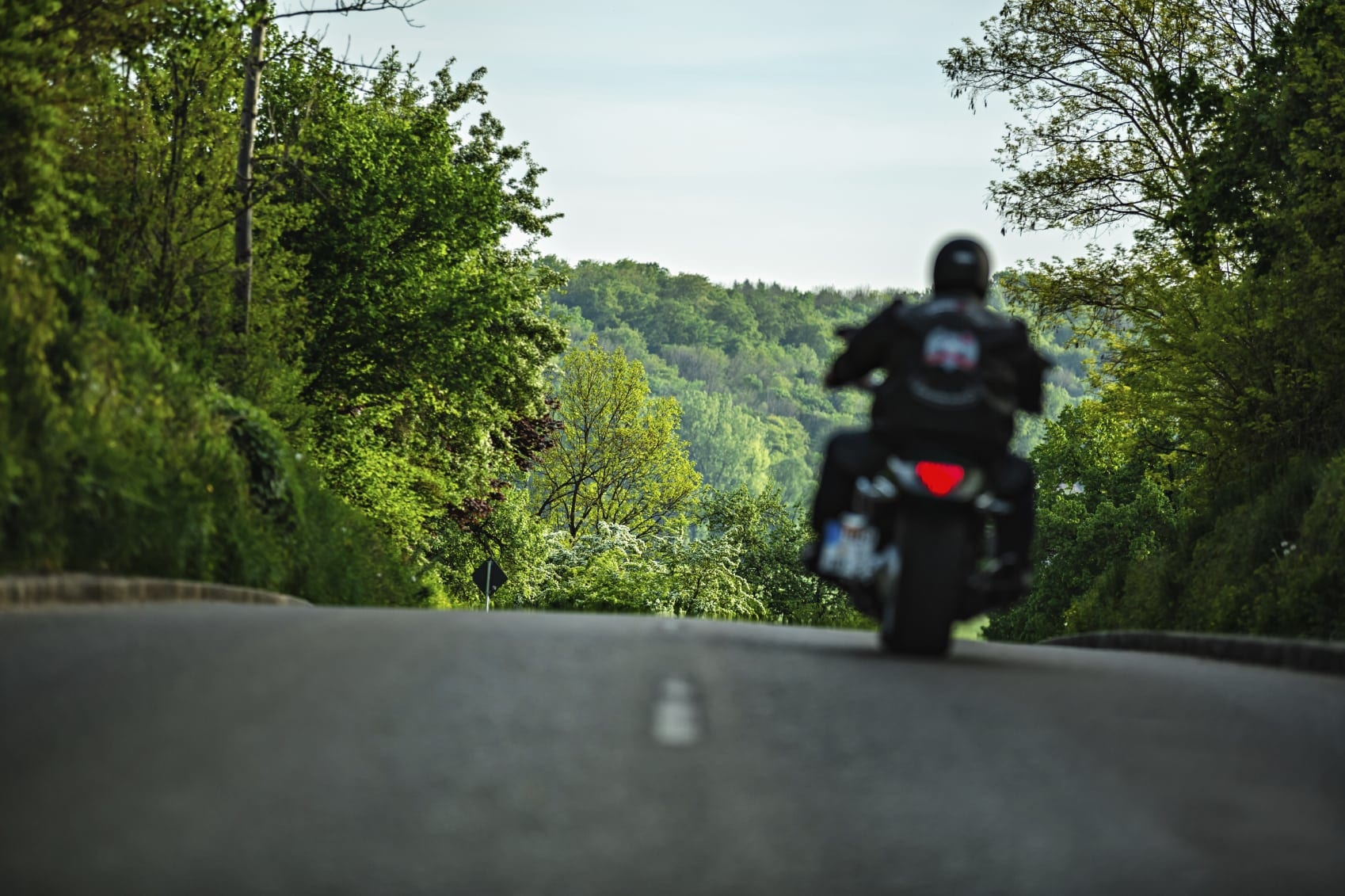 Motorcyclist Riding In Rural Area Stock Photo