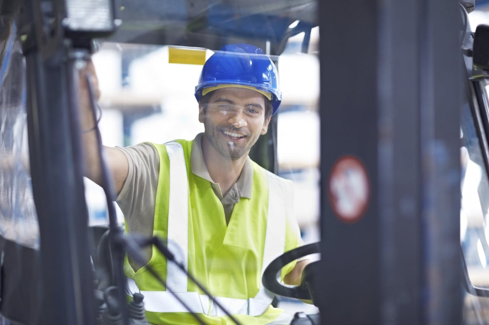 Man In Hard Hat Driving A Forklift Stock Photo