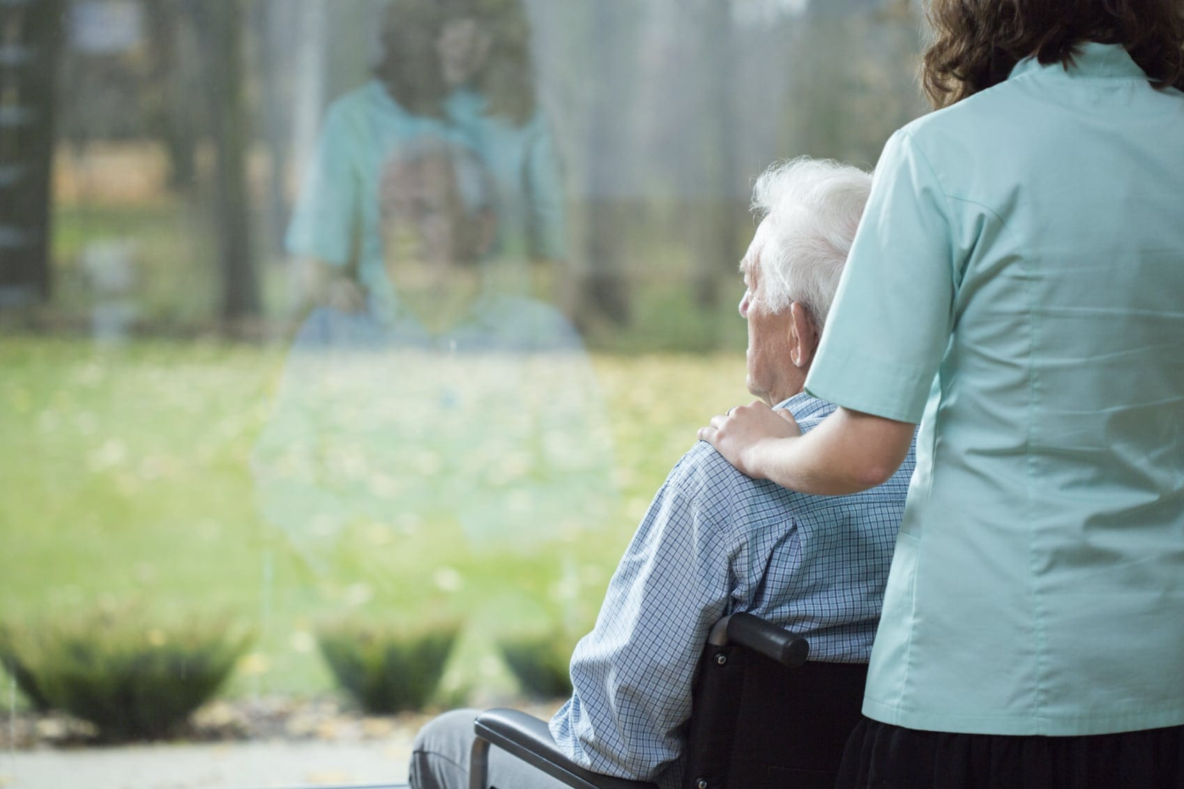 Daughter Comforting Elderly Father In Wheelchair Stock Photo
