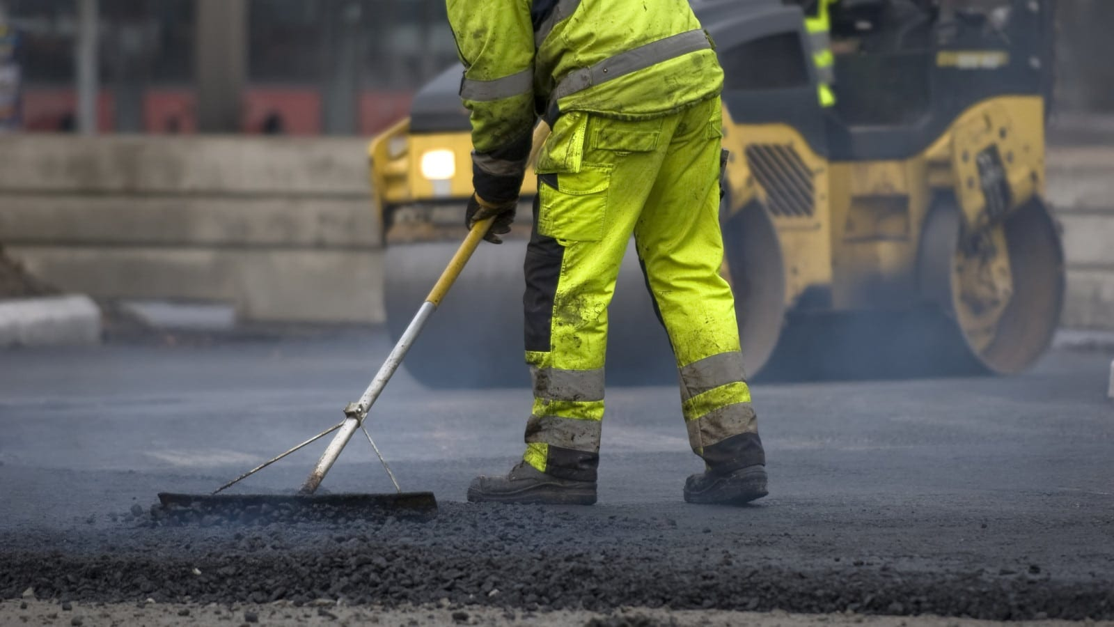 Construction Worker Repaving Blacktop Stock Photo