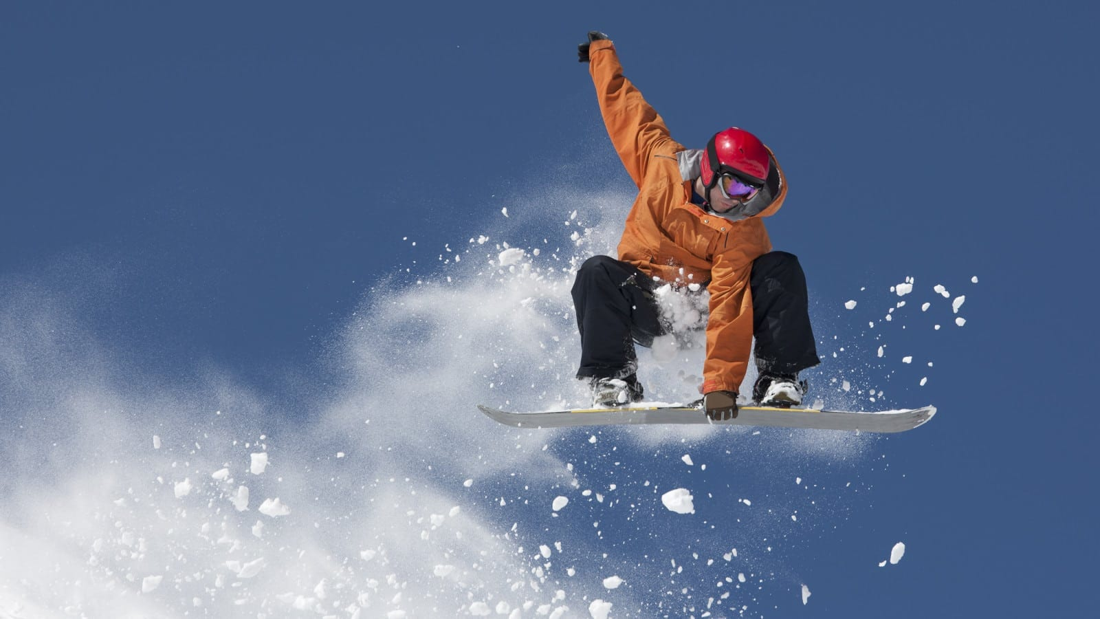 Young Man Snowboarding In The Snow Stock Photo