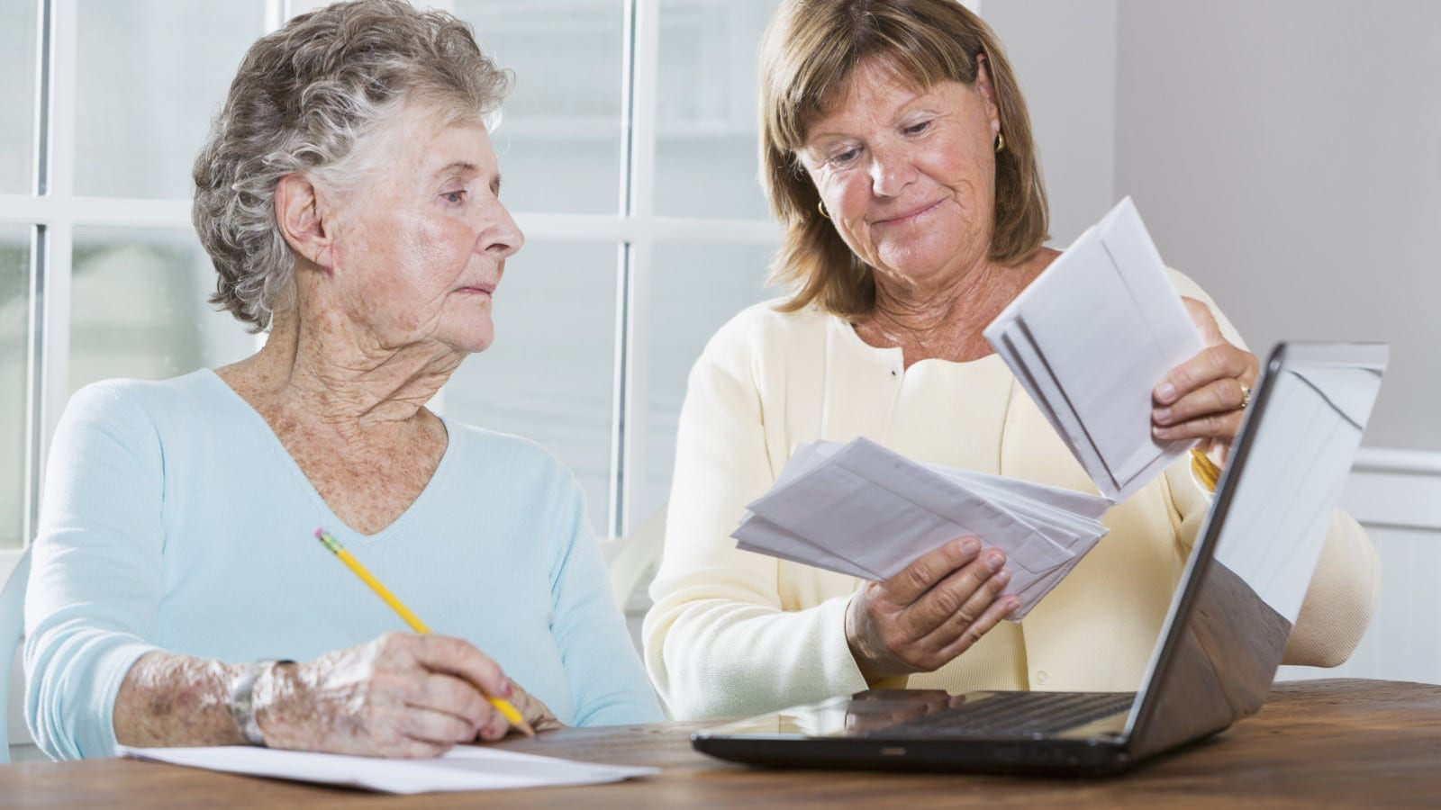 Elderly Mother And Daughter Examining Social Security Documents Stock Photo
