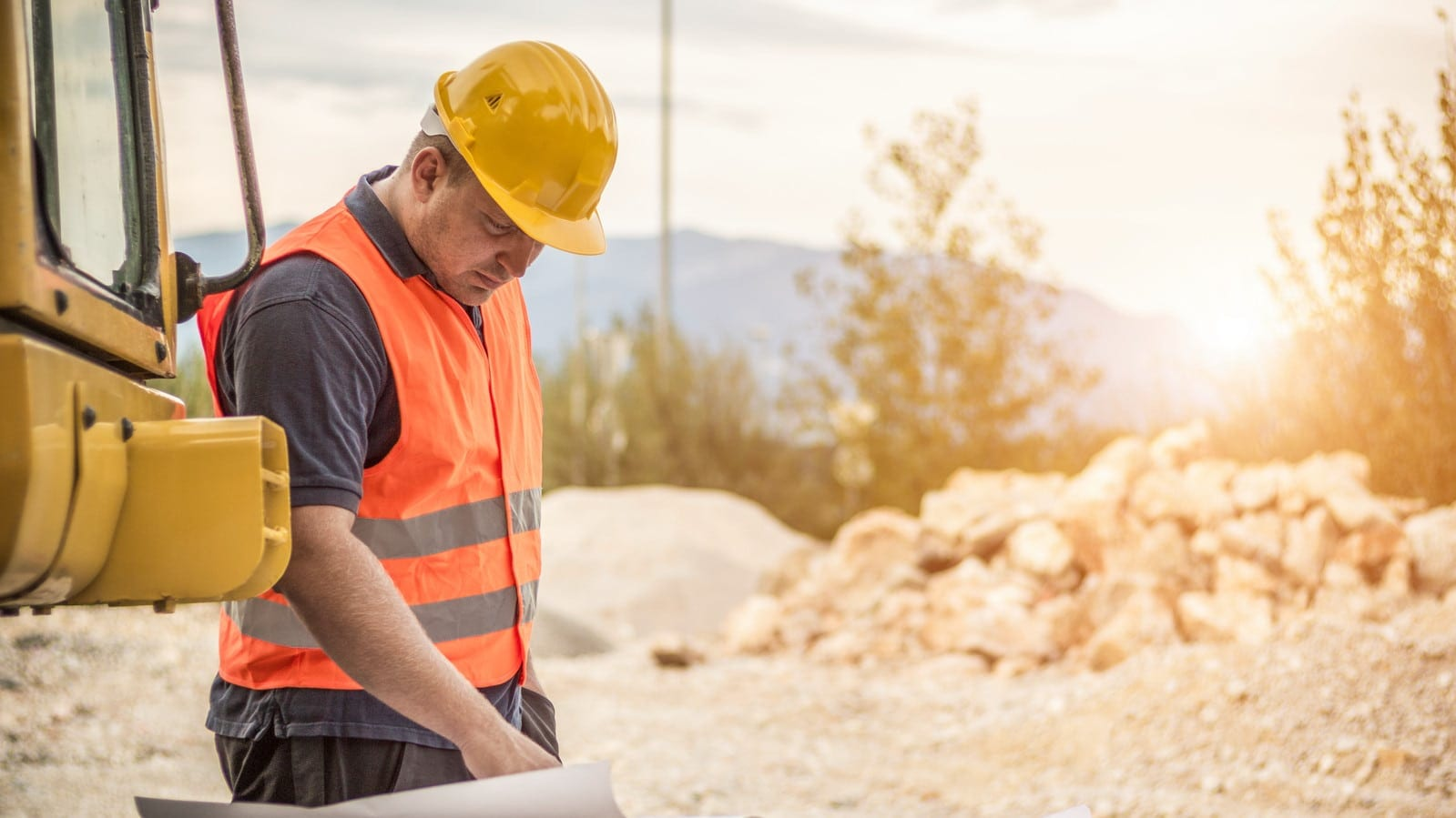 Construction Worker Examining Blueprints Stock Photo
