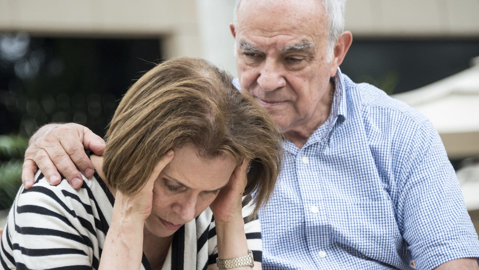 Elderly Man Consoling His Wife Stock Photo