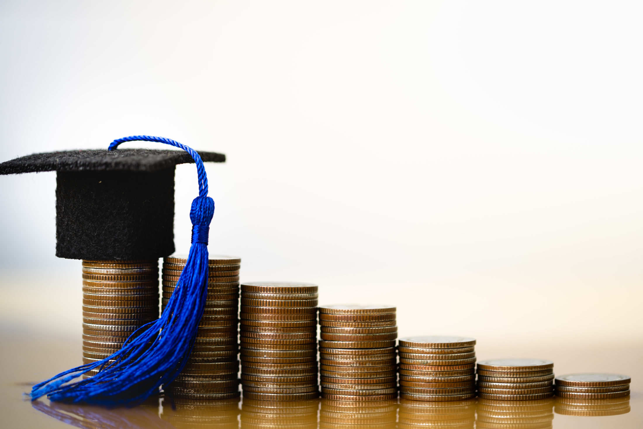 a graduation cap sitting on piles of coins symbolizing a college scholarship