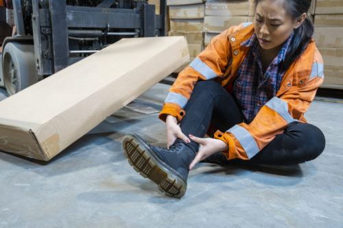 A woman in pain after suffering an on-the-job injury in a Colorado Springs warehouse.