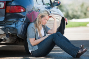 A woman leaning against her car after a car accident.